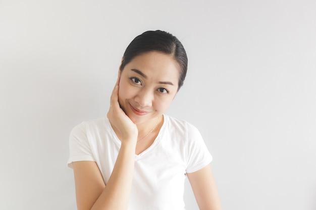 Lächeln und glückliche frau im weißen t-shirt. konzept des glücklichen und denkenden positivs.