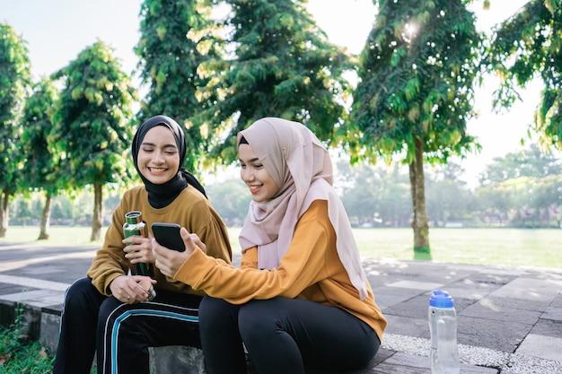 Lächeln zwei asiatische muslimische mädchen, die ein handy zusammen benutzen, wenn sie eine flasche nach dem gemeinsamen sport am nachmittag im park halten