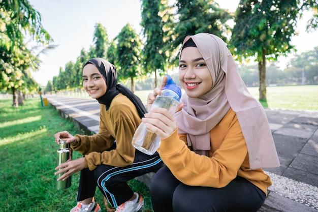Lächeln zwei asiatische muslimische mädchen, die wasser mit flaschen nach dem sport zusammen am nachmittag im park trinken