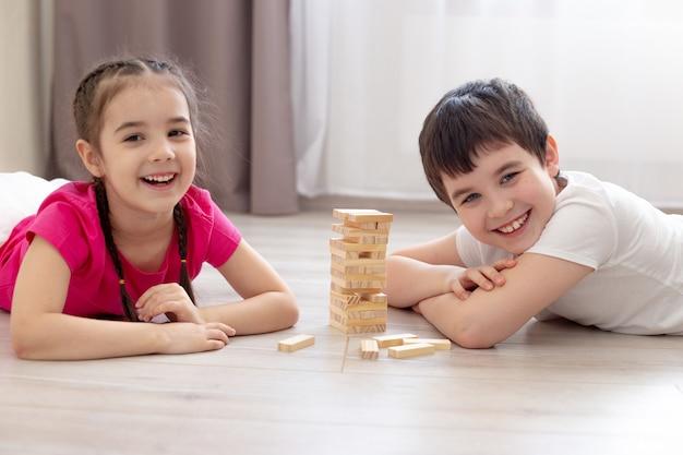Lächeln zwei kinder, junge und mädchen, holzspiel auf dem boden spielend