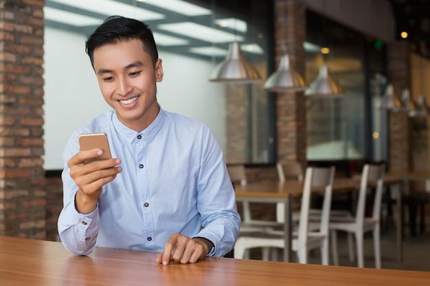 Lächelnd asiatischen mann, der smartphone im cafe tabelle