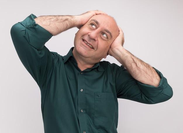 Lächelnd auf die seite schauender mann mittleren alters mit grünem t-shirt packte den kopf isoliert auf weißer wand on