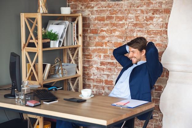 Lächelnd, ausruhend, sieht erfreut aus, erfolgreich. junger mann, manager, der nach der quarantäne in sein büro zurückkehrt, fühlt sich glücklich inspiriert. rückkehr ins normale leben. business, finanzen, emotionen konzept.