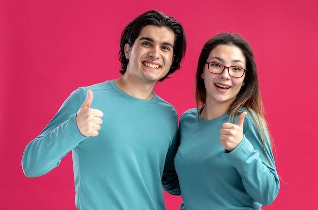Lächelnd aussehende kamera junges paar am valentinstag zeigt daumen nach oben isoliert auf rosa hintergrund