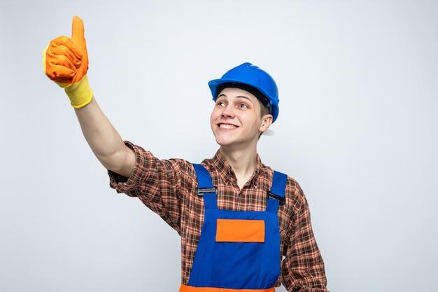 Lächelnd aussehende seite mit daumen nach oben junger männlicher baumeister, der uniform mit handschuhen trägt