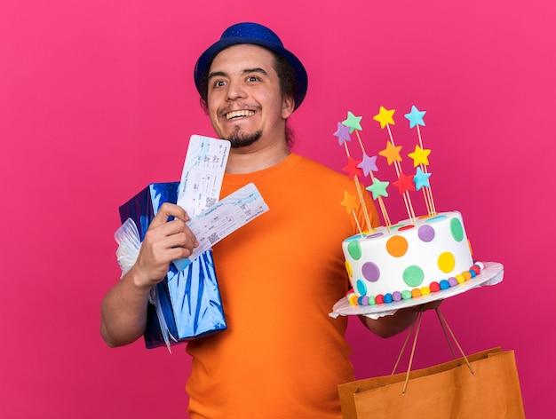 Lächelnd aussehender junger mann mit partyhut, der geschenkbox und kuchen mit tickets isoliert auf rosa wand hält