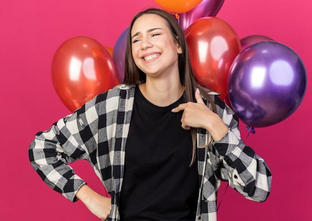 Lächelnd aussehendes junges schönes mädchen, das vor ballons steht, zeigt auf sich selbst isoliert auf rosa wand