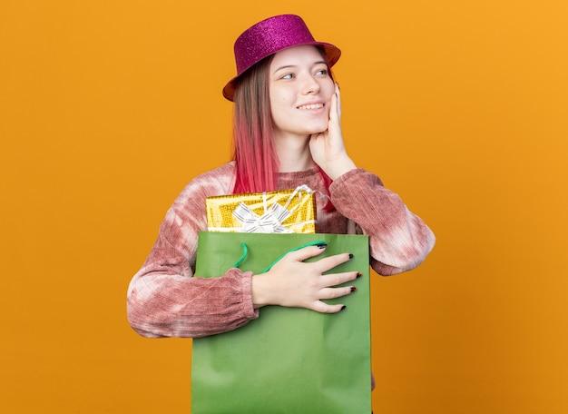 Lächelnd aussehendes junges schönes mädchen mit partyhut, das geschenktüte hält und hand auf die wange legt, isoliert auf oranger wand