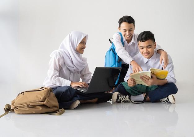 Lächelnd drei teenager in uniformen der junior high school sitzen auf dem boden und lernen zusammen mit ...