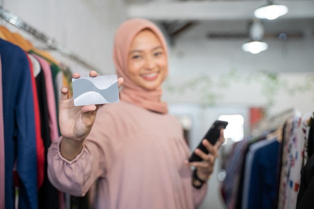 Lächelnd ein mädchen im schleier mit einer kreditkarte und einem handphone holding