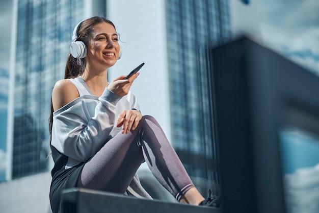Lächelnd erfreut attraktive kaukasische stilvolle sportliche junge frau in drahtlosen kopfhörern mit blick in die ferne