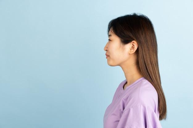 Lächelnd, fröhlich. porträt der jungen asiatischen frau auf blauer wand. schönes weibliches modell im lässigen stil. konzept der menschlichen emotionen, gesichtsausdruck, jugend, verkauf, anzeige.