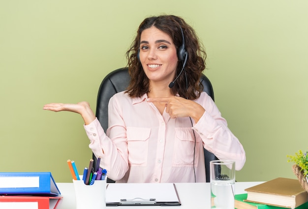 Lächelnd hübsche kaukasische callcenter-betreiberin auf kopfhörern, die am schreibtisch sitzen und bürowerkzeuge auf ihre leere hand zeigen