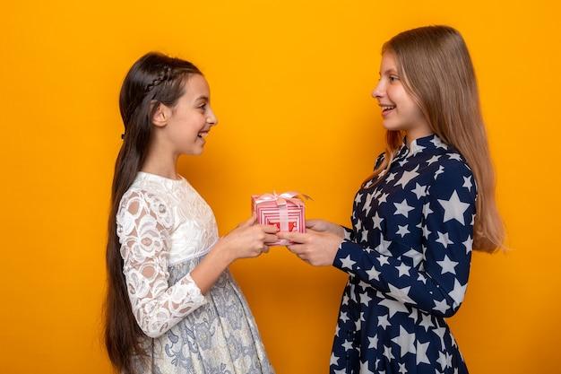 Lächelnd in der profilansicht stehen zwei kleine mädchen mit geschenk