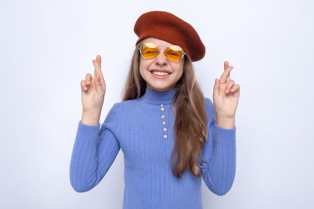 Lächelnd kreuzende finger schönes kleines mädchen mit brille mit hut