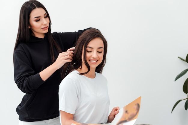Lächelnd liest attraktiver brunette eine zeitschrift, während ihr friseur ihr schönes haar kämmt