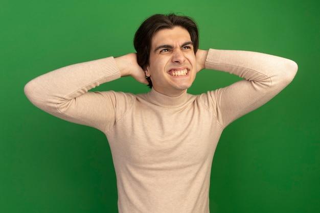 Lächelnd mit blick auf die seite junger gutaussehender kerl, der die hände auf den hals legt, isoliert auf grüner wand