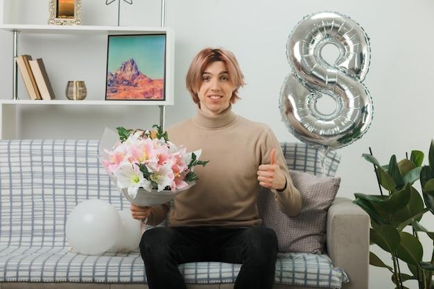 Lächelnd mit daumen hoch hübscher kerl am glücklichen frauentag mit blumenstrauß auf dem sofa im wohnzimmer sitzend