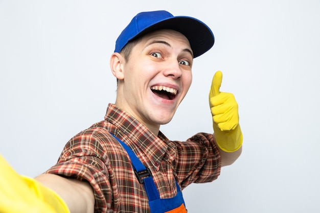 Lächelnd mit daumen nach oben junger putzmann in uniform und mütze mit handschuhen