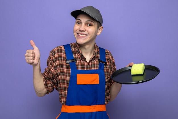 Lächelnd mit daumen nach oben junger putzmann in uniform und mütze mit schwamm auf tablett
