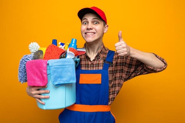 Lächelnd mit daumen nach oben junger reinigungsmann in uniform und mütze mit eimer mit reinigungswerkzeugen