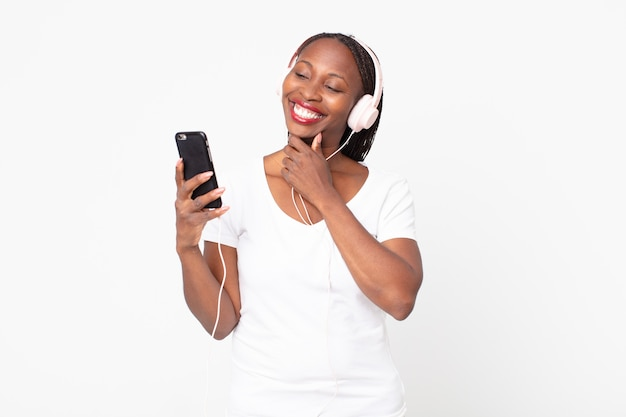 Lächelnd mit einem glücklichen, selbstbewussten ausdruck mit der hand am kinn mit kopfhörern und einem smartphone