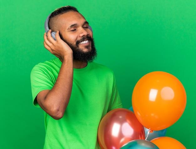 Lächelnd mit geschlossenen augen junger afroamerikanischer mann mit grünem t-shirt und kopfhörern, der hinter luftballons isoliert auf grüner wand steht