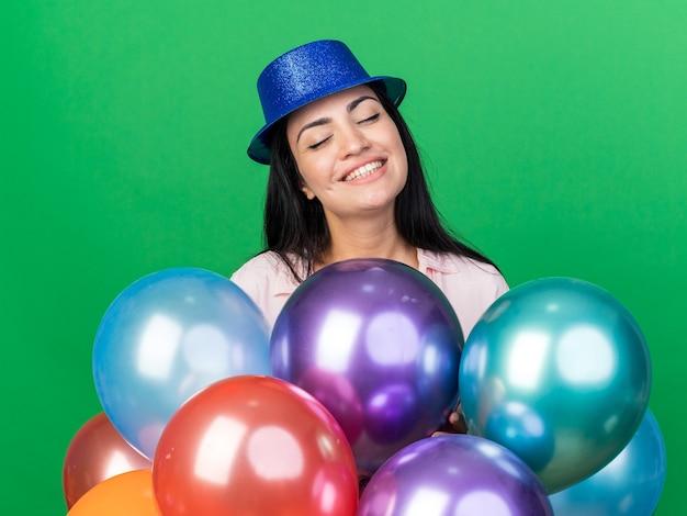 Lächelnd mit geschlossenen augen junges schönes mädchen mit partyhut, das hinter luftballons steht, isoliert auf grüner wand
