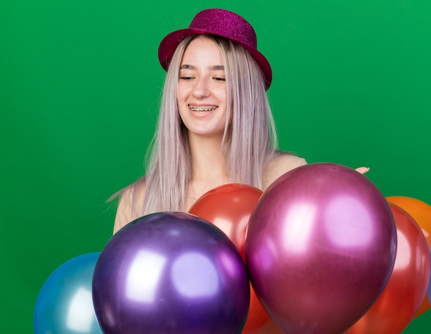Lächelnd mit geschlossenen augen junges schönes mädchen mit partyhut und hosenträgern, die hinter luftballons stehen