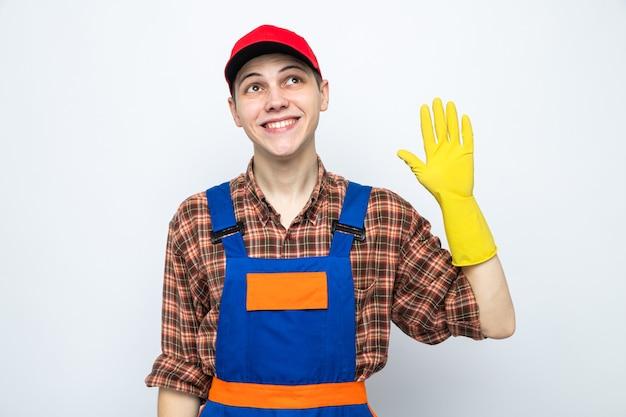 Lächelnd mit hallo geste junger putzmann in uniform und mütze mit handschuhen
