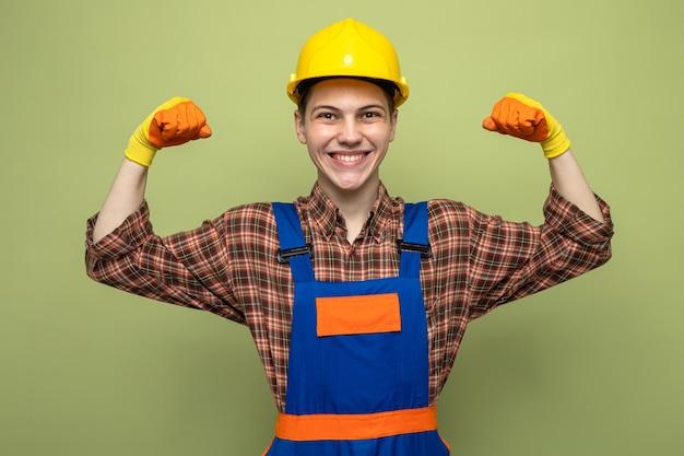 Lächelnd mit starker geste junger männlicher baumeister, der uniform mit handschuhen trägt