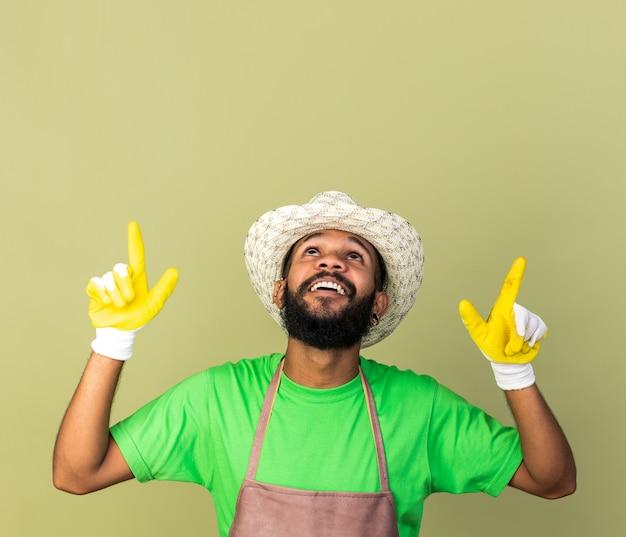 Lächelnd nachschlagender junger gärtner afroamerikanischer mann mit gartenhut mit handschuhen zeigt nach oben isoliert auf olivgrüner wand