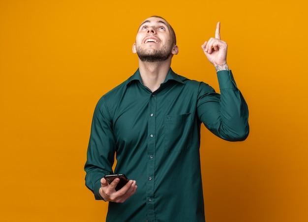 Lächelnd nachschlagender junger gutaussehender kerl mit grünem hemd, der telefonpunkte nach oben hält
