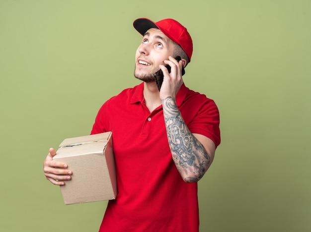 Lächelnd nachschlagender junger lieferbote in uniform mit mütze, der box hält, spricht am telefon