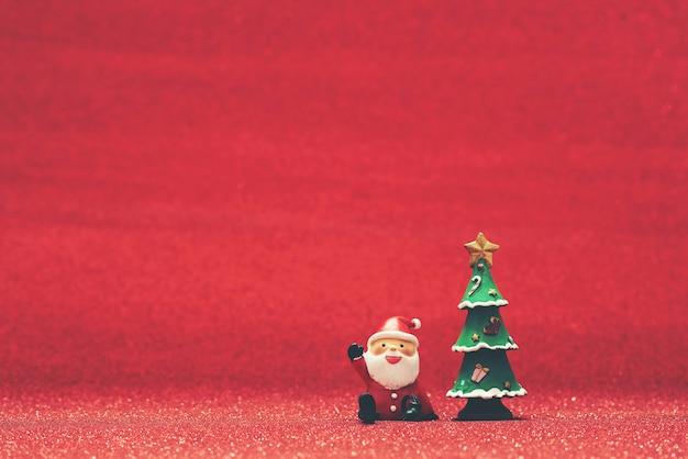 Lächelnd santa claus neben einem weihnachtsbaum und roten hintergrund