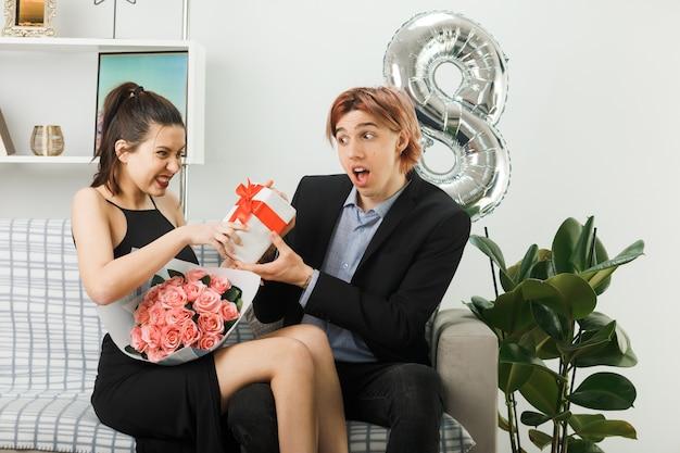 Lächelnd schaut sich das junge paar am glücklichen frauentag an, das geschenk mit blumenstrauß auf dem sofa im wohnzimmer hält