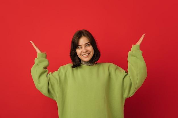 Lächelnd, taucht auf. porträt der kaukasischen frau auf rote wand mit exemplar isoliert. schönes weibliches modell im grünen hoodie. konzept der menschlichen emotionen, gesichtsausdruck