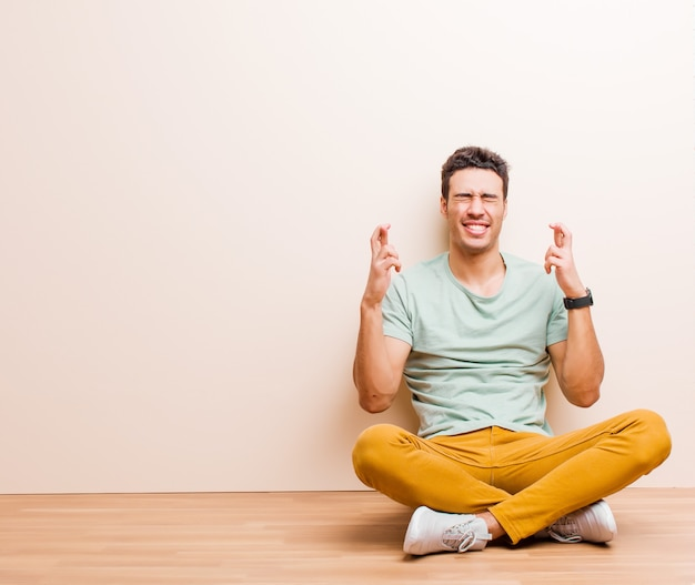 Lächelnd und ängstlich beide finger kreuzen, sich besorgt fühlen und viel glück wünschen oder hoffen