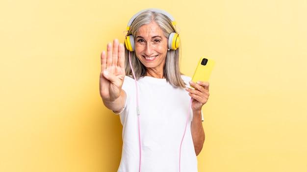 Lächelnd und freundlich aussehend, mit der hand nach vorne die nummer vier oder vier zeigen, mit kopfhörern rückwärts zählen