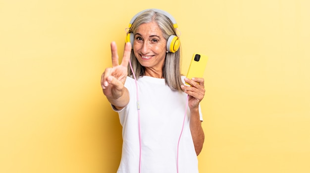 Lächelnd und freundlich aussehend, mit der hand nach vorne die nummer zwei oder die zweite zeigen, mit kopfhörern rückwärts zählen