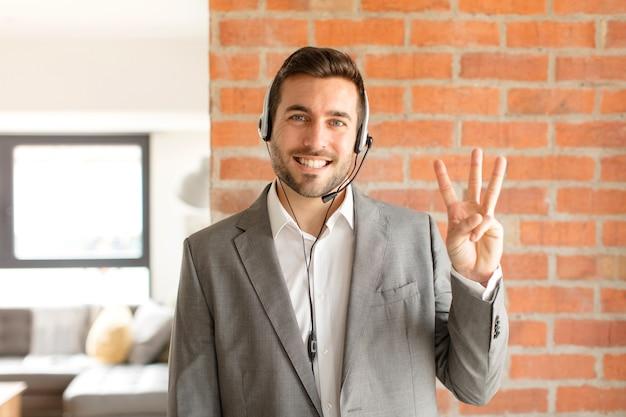 Lächelnd und freundlich aussehend, nummer drei oder dritte mit der hand nach vorne zeigend, herunterzählen