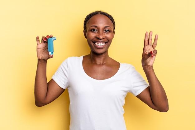 Lächelnd und freundlich aussehend, nummer drei oder dritte mit der hand nach vorne zeigend, rückwärts zählend. asthma-konzept