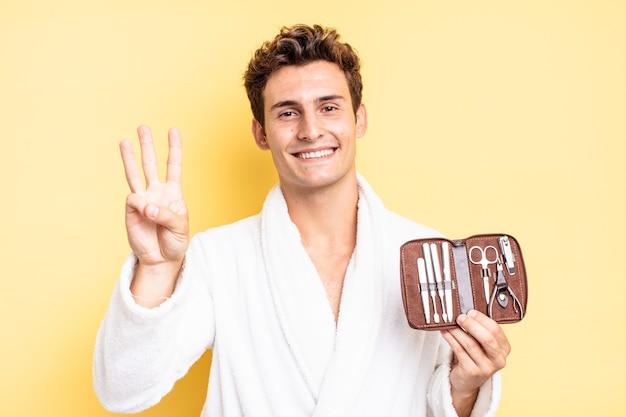 Lächelnd und freundlich aussehend, nummer drei oder dritte mit der hand nach vorne zeigend, rückwärts zählend. nagelwerkzeugkofferkonzept