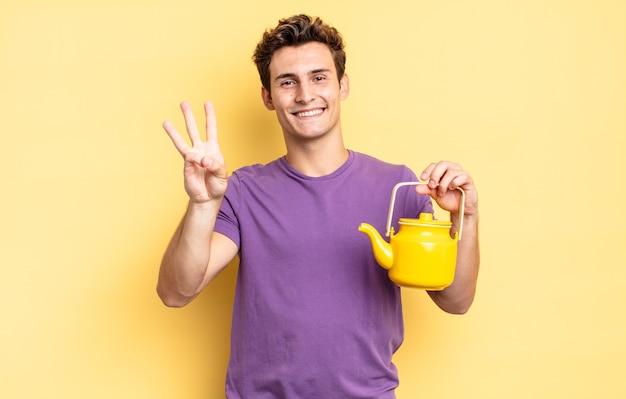 Lächelnd und freundlich aussehend, nummer drei oder dritte mit der hand nach vorne zeigend, rückwärts zählend. teekannenkonzept