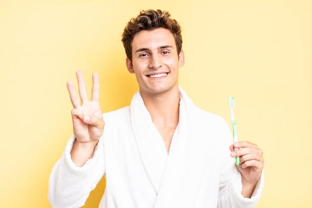 Lächelnd und freundlich aussehend, nummer drei oder dritte mit der hand nach vorne zeigend, rückwärts zählend. zahnbürstenkonzept