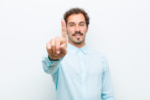 Lächelnd und freundlich aussehend, nummer eins oder zuerst mit der hand nach vorne zeigend, countdown
