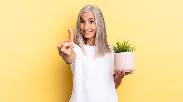 Lächelnd und freundlich aussehend, nummer eins oder zuerst mit der hand nach vorne zeigend, herunterzählen, eine zierpflanze halten