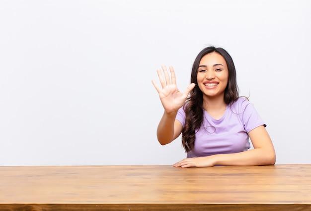 Lächelnd und freundlich aussehend, nummer fünf oder fünf mit der hand nach vorne zeigend, countdown