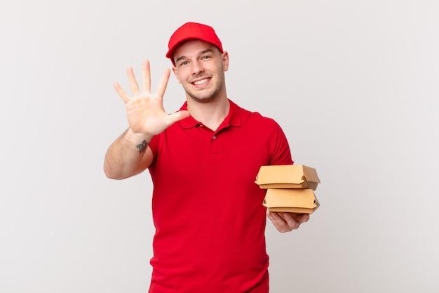 Lächelnd und freundlich aussehend, nummer fünf oder fünf mit der hand nach vorne zeigend, herunterzählen