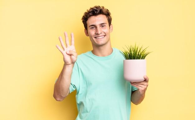 Lächelnd und freundlich aussehend, nummer vier oder vier mit der hand nach vorne zeigend, rückwärts zählend. dekoratives pflanzenkonzept